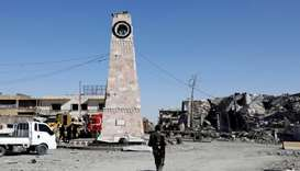 A fighter of Syrian Democratic Forces walks towards a clock tower in Raqqa, Syria.