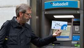 Joaquim Curbet poses with an envelope with 155 euros inside after withdrawing that amount of money f