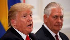 US President Donald Trump speaks as US Secretary of State Rex Tillerson (R) looks toward him