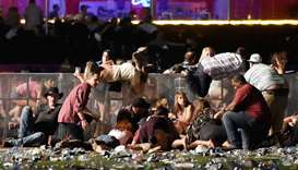 People scramble for shelter at the Route 91 Harvest country music festival after apparent gun fire w