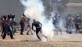 Protesters react to tear gas fired by riot policemen during a protest by opposition supporters again