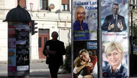 A man walks past presidential election campaign posters in Ljubljana