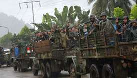 Philippine marines aboard their trucks flash the victory sign as they start their pull-out from the