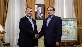 Saleh al-Arouri (L), Hamas deputy chief, shakes hands with Ali Shamkhani,