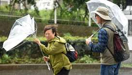 A woman have an umbrella turned inside out with strong wind in Tokyo