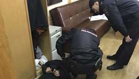 Policemen detain an intruder, who attacked Tatyana Felgengauer, anchor of Russian radio station Ekho