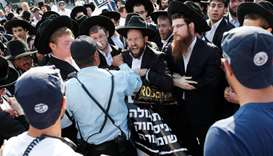 Israeli police stand guard as Ultra-Orthodox Jews demonstrate against Israeli army conscription outs