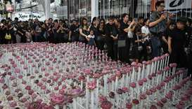 People walk past an elaborate lotus flower display made in honour of the late Thai king Bhumibol Adu
