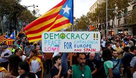 People wave separatist Catalonian flags and placards during a demonstration organised by Catalan pro