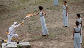 Greek actress Katerina Lehou, playing the role of High Priestess passes the flame to Greek cross cou