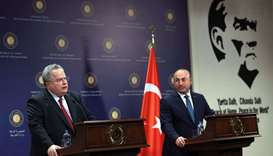 Turkish Foreign Minister Mevlut Cavusoglu (R) and Greek Foreign Minister Nikos Kotzias (L) hold a jo