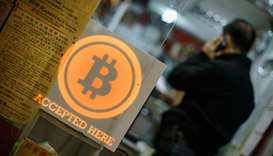 A man talking on a mobile phone in a shop displaying a bitcoin sign during the opening ceremony of t