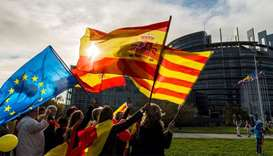 Women hold Spanish, Catalan and European flags during a demonstration against Catalonia's independen