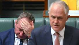 Australian Deputy Prime Minister Barnaby Joyce reacts as he sits behind Australian Prime Minister Ma