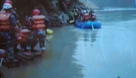 Security personnel searching for missing passengers of the bus that plunged into Trishuli River.