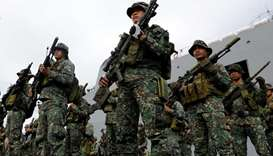 Philippine marines from the Marine Battalion Landing Team stand to attention during their arrival fr