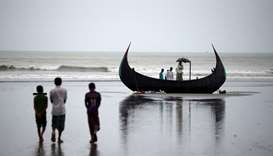People look at a boat that capsized with a group of Rohingya refugees in it at Bailakhali, near Cox'