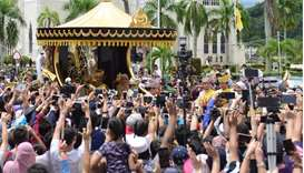 Brunei's Sultan Hassanal Bolkiah waves to people as he passes in a procession to mark his golden jub