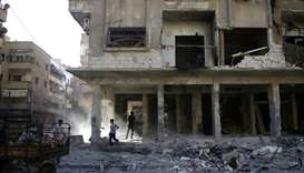 Men inspect damages after an airstrike on the rebel-held city of Douma, in the eastern Damascus subu
