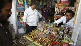 An Indian fireworks vendor serving customers at his shop in New Delhi