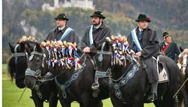 Men in traditional dresses taking part in Coloman ride sit on their festively decorated horses