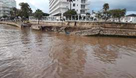 People walk along the damaged waterfront after a storm on the island of Majorca, Spain