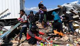 Indonesian salvage useable items from debris of collapsed building in Palu, Indonesia's Central Sula