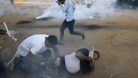 Palestinians react from tear gas fired by Israeli troops during a protest calling for lifting the Is