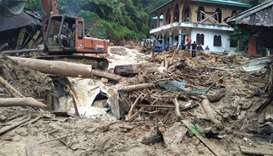 People use a heavy equipment to remove debris after flash floods hit the Saladi village in Mandailin