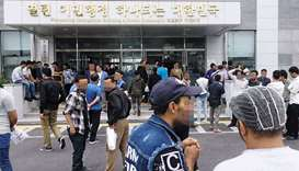 Yemeni asylum seekers wait in front of an immigration office on Jeju Island