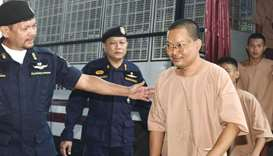 Disgraced monk Wiraphon Sukphon, third left, arrives with other prisoners at a criminal court in Ban