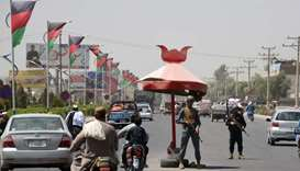 Afghan policemen stand guard at a checkpoint in Kandahar