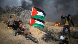 Palestinian demonstrators take cover next to Israeli wire during a protest calling for lifting the I