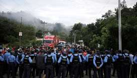 Honduran police officers block the access to the Agua Caliente border with Guatemala as Honduras' mi