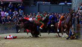 Jockeys fall off their horse during the race