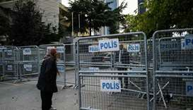 A woman stands next to police barriers, in front of the Saudi consulate in Istanbul