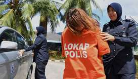 British national Samantha Jones (C) is escorted by a police officer as she arrives at a court in Lan