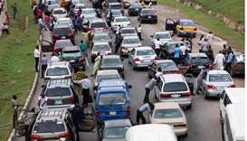 People wait next to their cars on the Abuja - Nasarawa road due to clashes between Nigerian soldiers