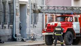 A Russian firefighter walks near a fire-engine at building housing the FSB security service in Arkha
