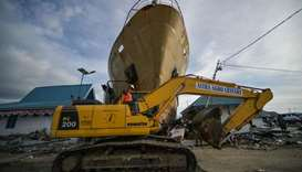 A heavy equipment crosses near a washed out passenger ferry in Wani, Indonesia's Central Sulawesi