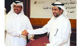 HE Al-Sada shaking hands with al-Derham after signing the MoU for co-operation between the Ministry