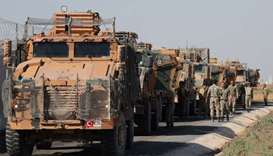 Turkish soldiers stand near military trucks in the village of Yabisa, near the Turkish-Syrian border