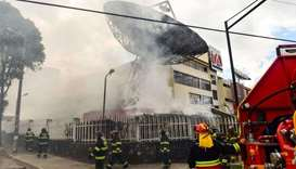 Firefighters work to extinguish a fire at Ecuadorean TV station Teleamazonas offices in Quito