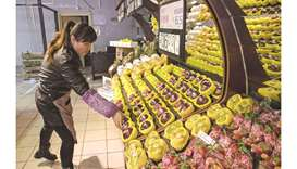 An employee arranges imported American apples for sale at a grocery store in Beijing. US agriculture