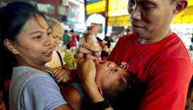 A health worker administers free polio vaccine to a child during a government-led mass vaccination p