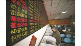 Investors look at computer screens showing stock information at a brokerage house in Shanghai. The C