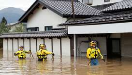 Police search a flooded area in the aftermath of Typhoon Hagibis, which caused severe floods at the