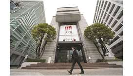 A pedestrian walks past the Tokyo Stock Exchange building in Japan. The Nikkei 225 closed up 1.7% to
