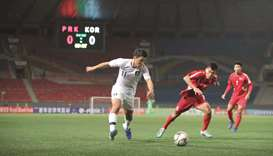 South Korea's Hwang Hee-chan (left) and North Korea's Kim Chol Bom vie for the ball 