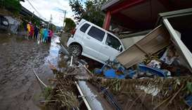 A car sits next to a badly damaged home in Nagano after Typhoon Hagibis hit Japan
